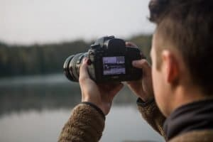 person taking photo of mountains with a 4k Ultra HD video camera